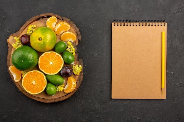 Vista superior de tangerinas verdes frescas com feijoas na mesa escura