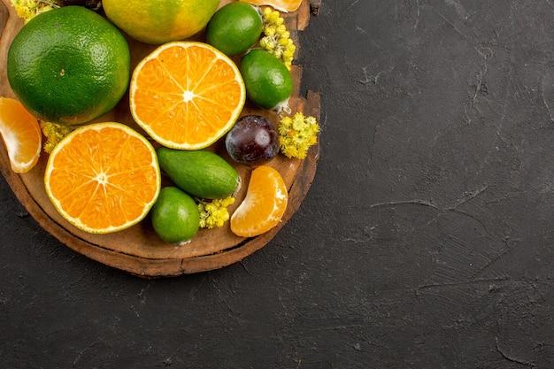 Vista superior de tangerinas verdes frescas com feijoas no escuro