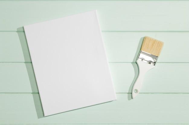 Vista superior de tela vazia e pincel de pintura