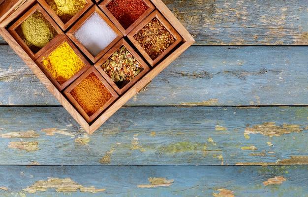 Vista superior de temperos de especiarias coloridas em caixa de madeira.