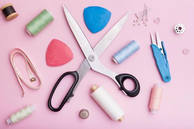 Vista superior de tesouras, fios e material de costura em um fundo rosa. o conceito de costura de roupas.