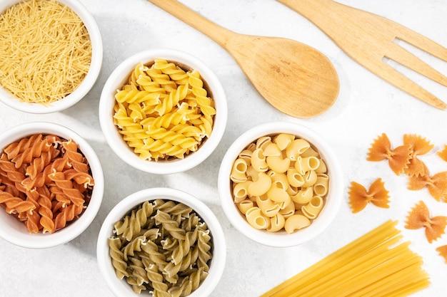 Vista superior de tigelas com massas não cozidas variadas. comida mediterrânea