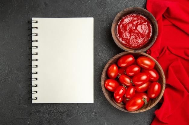 Vista superior de tigelas com tomate cereja e toalha vermelha de ketchup, um caderno em fundo escuro