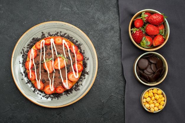 Vista superior de tigelas de bolo de avelã, morango e chocolate na toalha de mesa e bolo com chocolate e morango na mesa preta