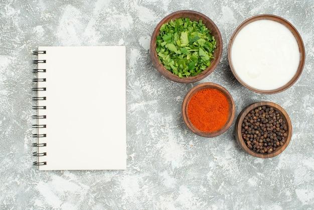 Vista superior de tigelas de especiarias, especiarias, ervas, pimenta preta e creme de leite, ao lado de um caderno branco na mesa cinza