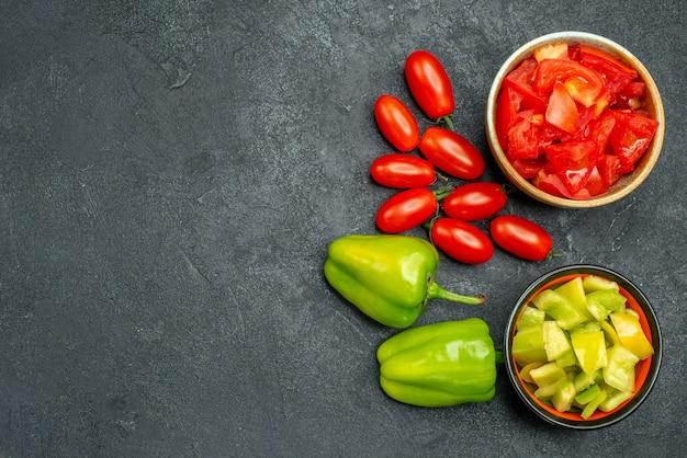 Vista superior de tigelas de pimentão e tomate com legumes ao lado e espaço livre para o seu texto sobre fundo verde escuro