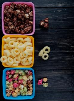 Vista superior de tigelas de pipocas como skittles e chocolate com cereais pop milho na superfície de madeira preta