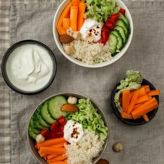 Vista superior de tigelas de salada vegetariana com cuscuz e iogurte