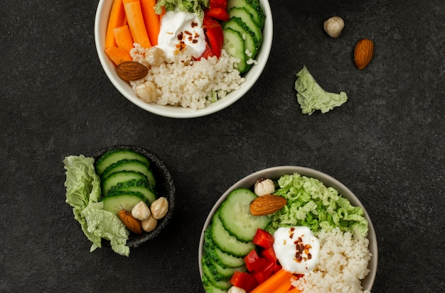 Vista superior de tigelas de salada vegetariana com cuscuz e pepino
