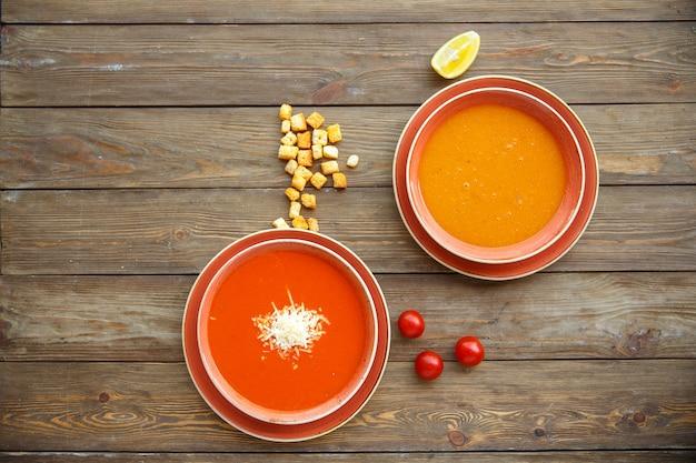 Vista superior de tigelas de sopa com sopas de tomate e lentilha em fundo de madeira