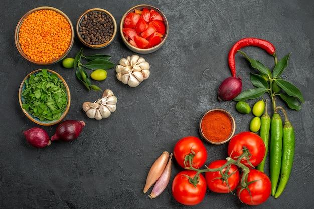 Vista superior de tigelas de tomates de lentilha, cebola, alho, ervas, temperos, tomates, pimentas