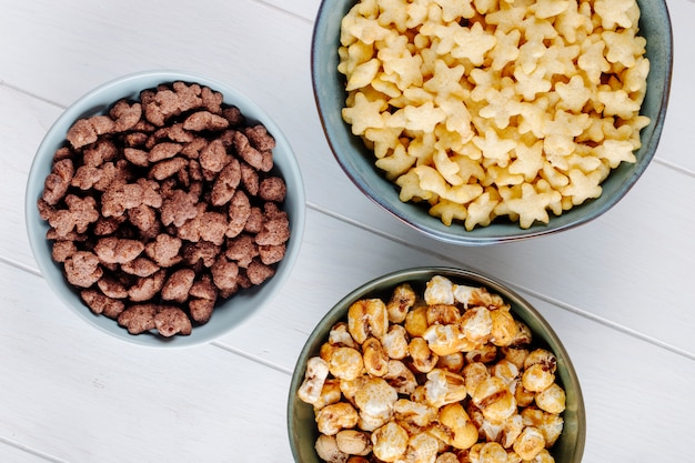 Vista superior de tigelas de vários cereais e pipoca de caramelo doce em fundo branco de madeira
