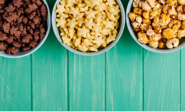 Vista superior de tigelas de vários cereais e pipoca de caramelo doce sobre fundo verde de madeira, com espaço de cópia