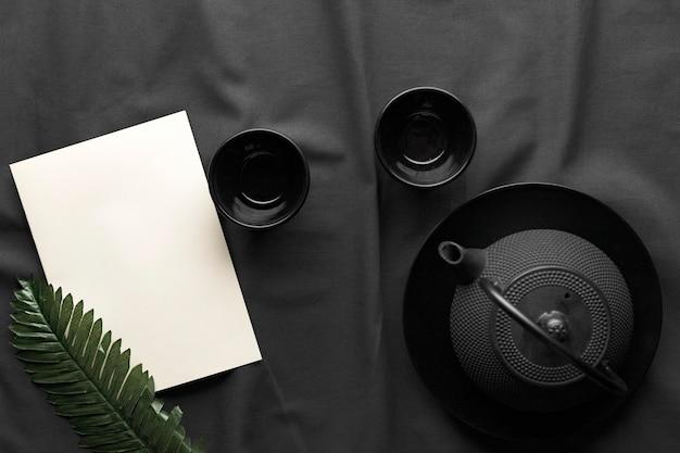 Vista superior de tigelas escuras com bule e folha