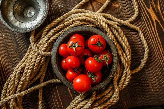 Vista superior de tomate cereja em uma tigela de madeira com corda em cima da mesa