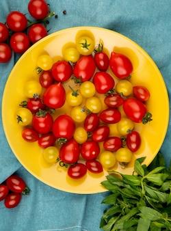 Vista superior de tomates amarelos e vermelhos no prato com folhas de hortelã verde na mesa de pano azul
