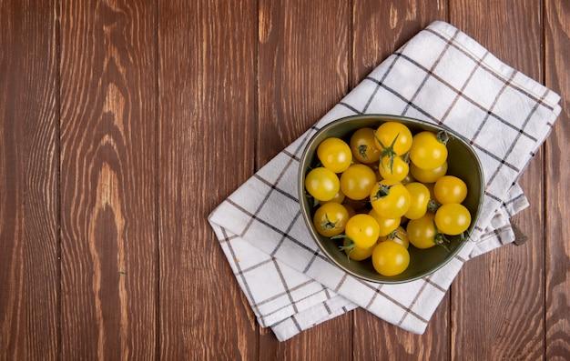 Vista superior de tomates amarelos em tigela no pano no lado direito e mesa de madeira