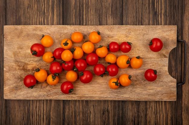 Vista superior de tomates cereja coloridos frescos isolados em uma placa de cozinha de madeira em uma parede de madeira