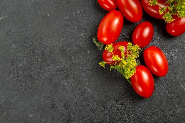 Vista superior de tomates cereja e flores de endro no canto superior direito de um terreno escuro com espaço de cópia