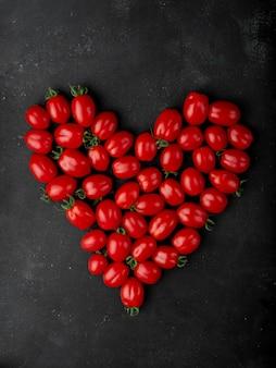 Vista superior de tomates cereja frescos dispostos em forma de coração em fundo preto