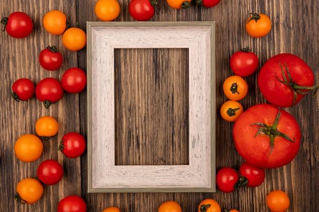 Vista superior de tomates-cereja frescos, vermelhos e laranja, isolados em uma parede de madeira com espaço de cópia