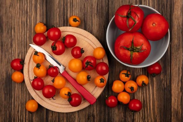 Vista superior de tomates cereja frescos vermelhos e laranja isolados em uma placa de cozinha de madeira com uma faca com tomates de tamanho grande em uma tigela na parede de madeira