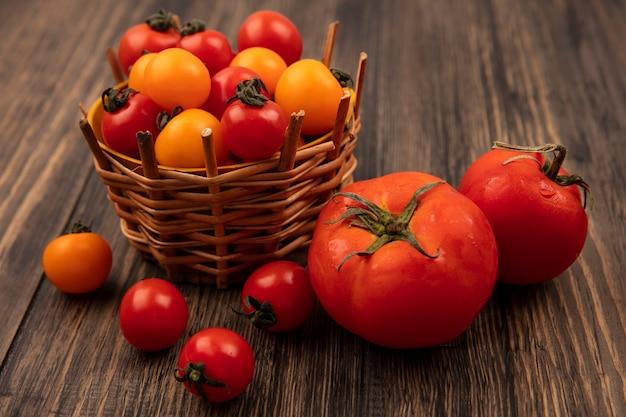 Vista superior de tomates cereja vermelhos e laranja em um balde com grandes tomates macios isolados em uma superfície de madeira