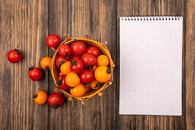 Vista superior de tomates cereja vermelhos e laranja em um balde com tomates isolados em uma parede de madeira com espaço de cópia