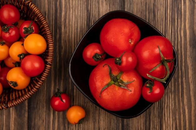 Vista superior de tomates cereja vermelhos e laranja suaves em um balde com tomates grandes em uma tigela na parede de madeira