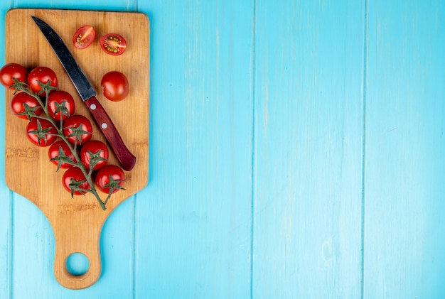Vista superior de tomates cortados e inteiros com faca na tábua em azul com espaço de cópia