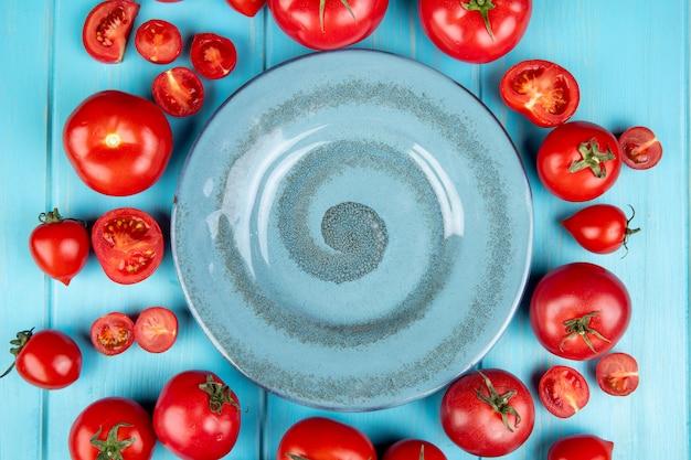 Vista superior de tomates cortados e inteiros em torno do prato na superfície azul