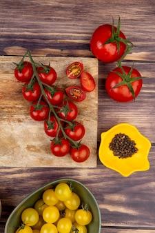 Vista superior de tomates cortados e inteiros na tábua com outras sementes de pimenta preta na superfície de madeira