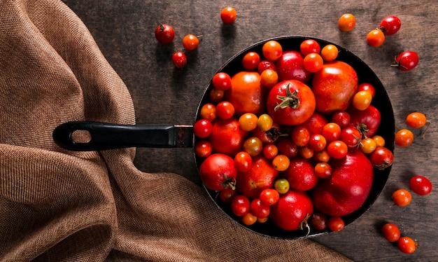 Vista superior de tomates de outono em uma panela com pano