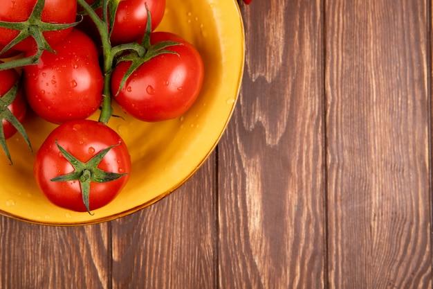 Vista superior de tomates em uma tigela no lado esquerdo e madeira com espaço de cópia