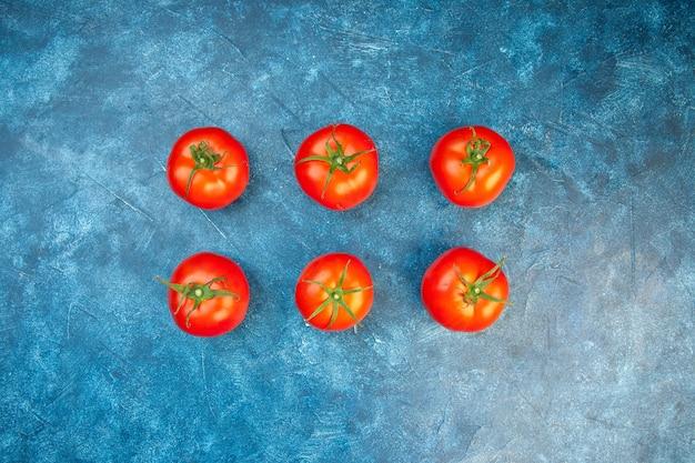 Vista superior de tomates frescos alinhados na mesa azul