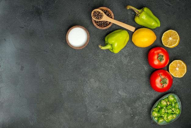 Vista superior de tomates frescos com pimentão e limão em fundo escuro