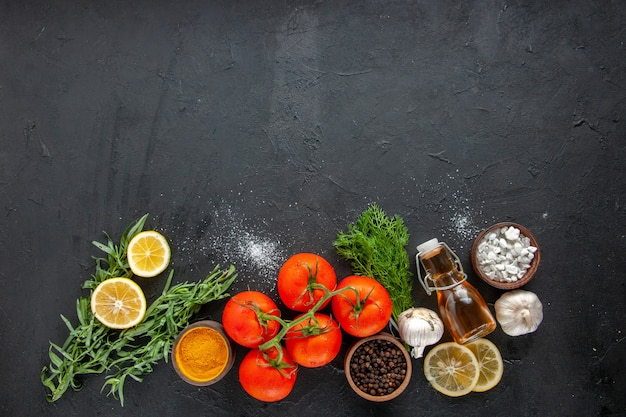 Vista superior de tomates frescos com rodelas de limão na mesa escura