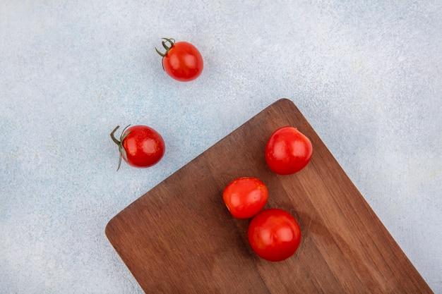 Vista superior de tomates frescos e cereja vermelhos em uma placa de madeira da cozinha na superfície branca