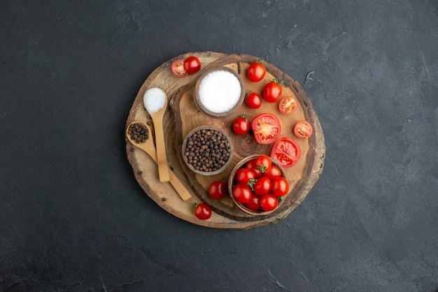 Vista superior de tomates frescos e especiarias na placa de madeira na superfície preta