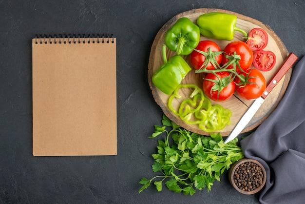 Vista superior de tomates frescos e pimentões verdes em um caderno de placa de madeira na superfície preta