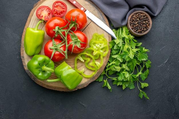 Vista superior de tomates frescos e pimentões verdes no pacote verde da placa de madeira na superfície preta