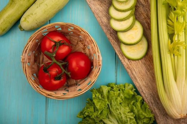 Vista superior de tomates frescos em um balde com abobrinhas picadas em uma placa de cozinha de madeira com aipo com alface isolado em uma superfície de madeira azul