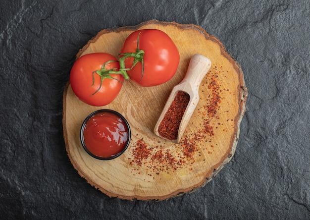 Vista superior de tomates frescos maduros com ketchup e pimenta na placa de madeira sobre o fundo preto.