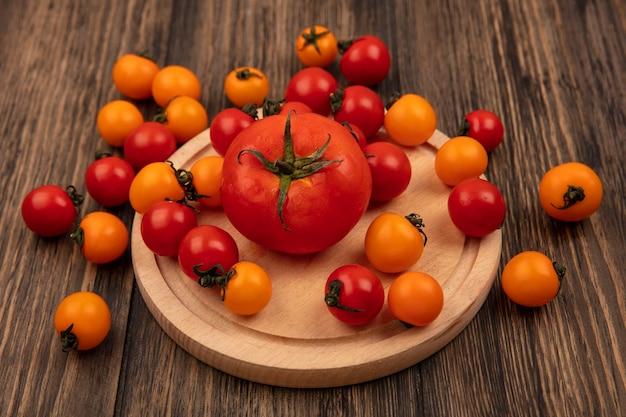 Vista superior de tomates frescos vermelhos e laranja isolados em uma placa de cozinha de madeira em uma parede de madeira