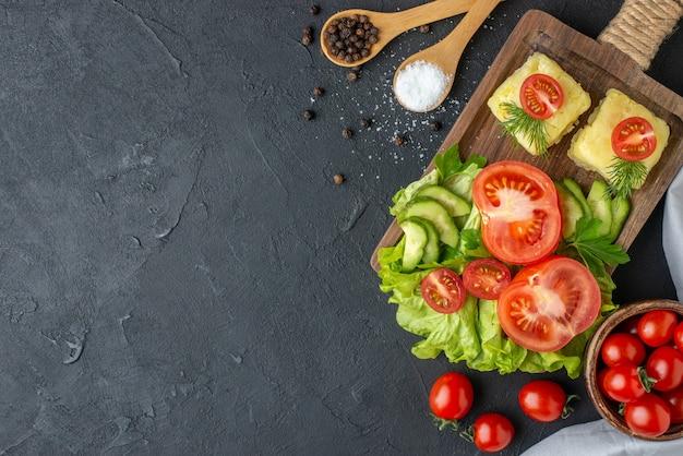 Vista superior de tomates inteiros frescos e queijo de pepino cortados em talheres de tábua de madeira com especiarias em colheres na superfície preta