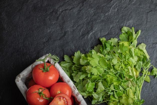 Vista superior de tomates maduros frescos na cesta e folhas de coentro em fundo preto.
