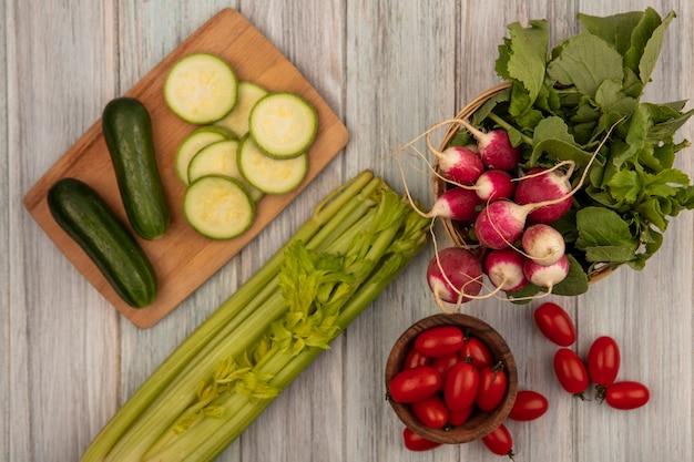 Vista superior de tomates orgânicos em uma tigela de madeira com rabanetes em um balde com pepinos em uma placa de cozinha de madeira com tomates e aipo isolado em uma superfície cinza de madeira