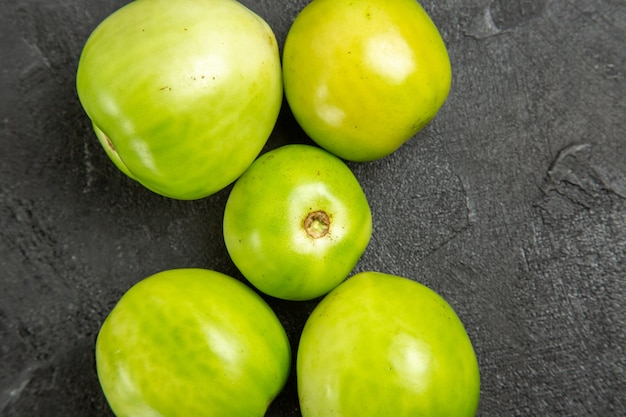 Vista superior de tomates verdes na mesa escura com espaço de cópia