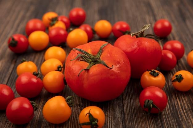 Vista superior de tomates vermelhos arredondados com tomates cereja laranja e vermelho isolados em uma superfície de madeira