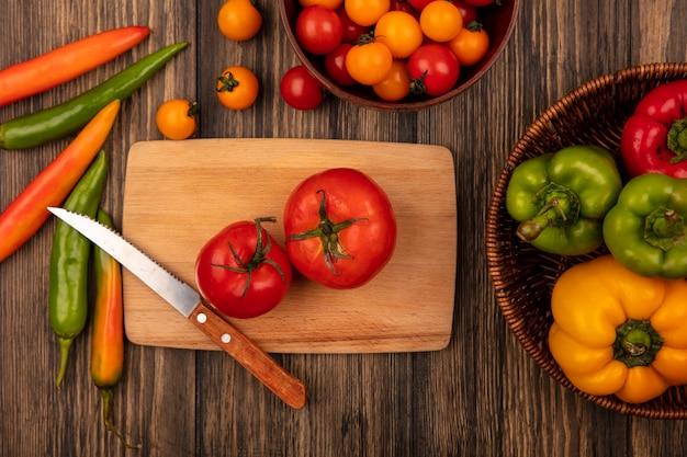 Vista superior de tomates vermelhos com sabor grande em uma placa de cozinha de madeira com uma faca com tomate cereja em uma tigela de madeira e pimentões em um balde em uma parede de madeira
